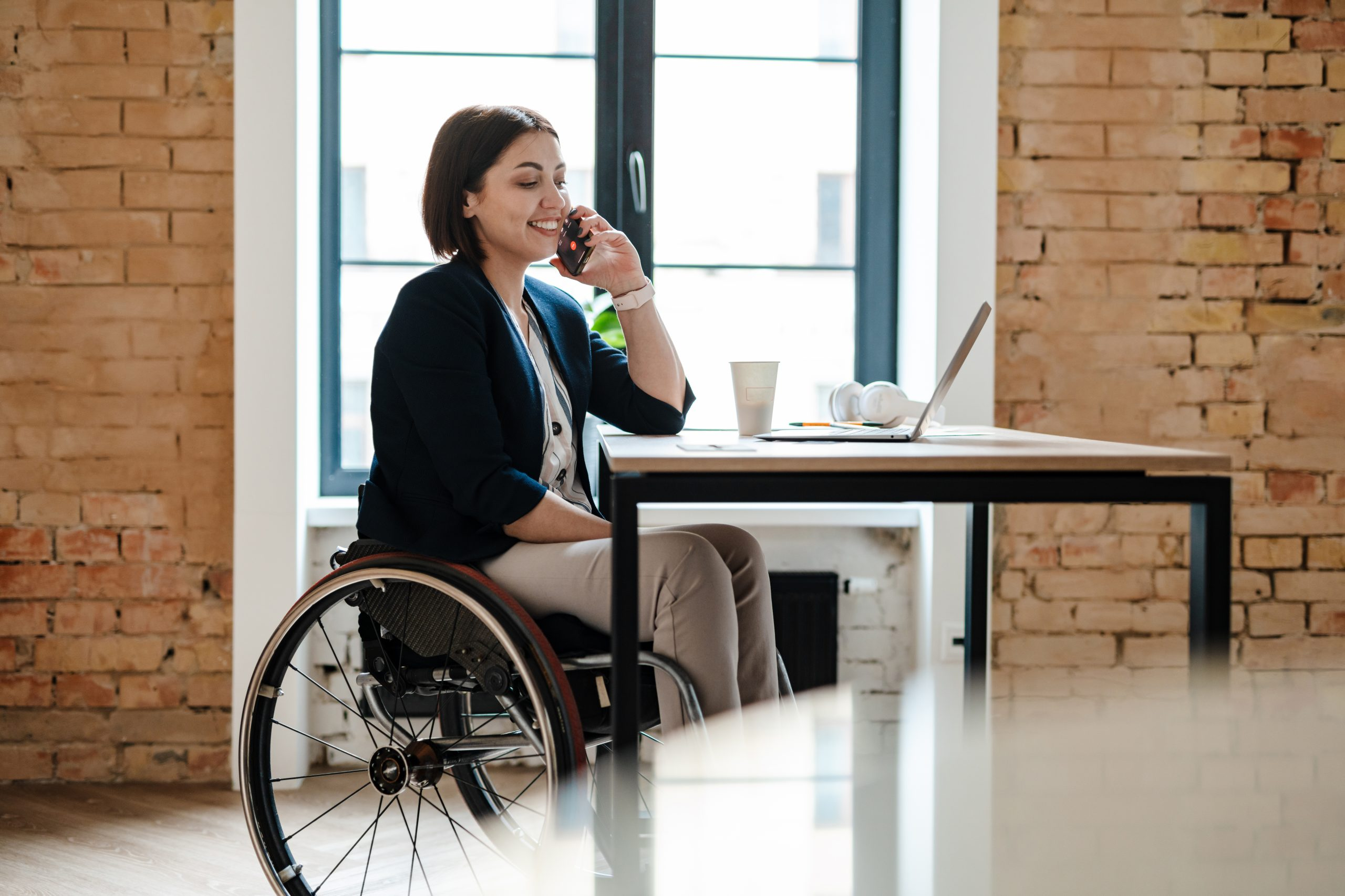 Young disabled business woman in wheelchair working at office desk with a laptop.