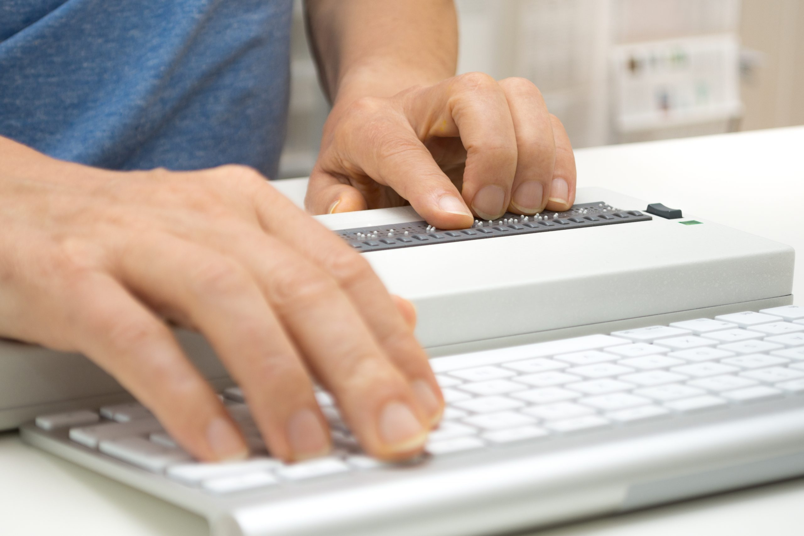 Cropped photo of an individual working on computer with assistive technology; braille display and keyboard.